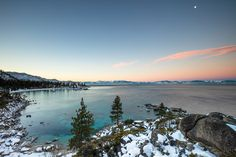 """""""Sand Harbor Sunrise 1"""" - Photograph of Sand Harbor in the distance shot at sunrise, the moon can be seen in the photo."""