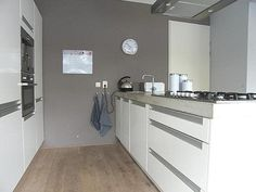 Grijze muur, Witte keuken met grijzen blad. Let op stopcontact: niet mooi afgewerkt. Qua indeling: Waar zou geschikte plek zijn voor koffie/thee?