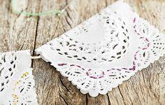 É só dobrar ao meio e prender com um pinguinho de cola que as toalhinhas de papel rendado se transformam em românticas bandeirinhas. Quer caprichar mais? Com linha e agulha, dê um toque colorido nelas