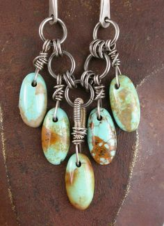 Wire wrapped drops of Royston Turquoise, dangling from a sterling chain with hand forged twisted links.