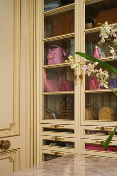 The homeowner wanted a closet large enough to hold her entire wardrobe, including shoes and accessories. In response, the designers created a well-organized French-inspired space that concealed her entire wardrobe behind closed doors—including a special closet just for shoes. A large center island and glass-front shelves and drawers keep handbags and accessories organized.