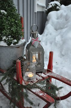 Rustic Christmas...old red sled, snow, & pine...lighted lanterns.