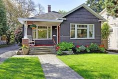 Ingredients for curb appeal: Tasteful garden and hanging plant, front porch with rocking chair, mowed lawn, bright white trim