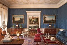Eighteenth-century harbor scenes are displayed in the living room. The walls and the sofa are covered in a silk damask, the inlaid commodes flanking the doorway are 18th-century Neapolitan, and the carpet is an antique Oushak.