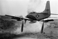 Flying low over the jungle, an A-1 Skyraider drops 500-pound bombs on a Viet Cong position below as smoke rises from a previous pass at the target, Dec. 26, 1964. (AP Photo/Horst Faas) #