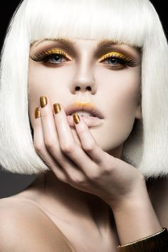 Beautiful girl in a white wig, with gold makeup and nails. Celebratory image. Beauty face. poster