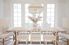 @jshomedesign- Ballard designs Dayna chairs. Trestle dining table. Ro Sham Beaux chandelier. Beaded chandelier. French doors. Coastal style. Hamptons style. Coastal chic. Coastal dining room. Wing back chairs.