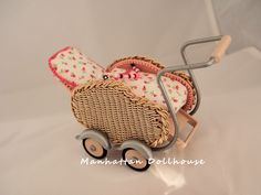 Miniature wicker baby stroller with moveable headrest.