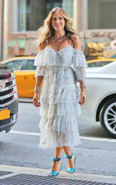 Sarah Jessica Parker in a layered tulle off-the-shoulder dress by Needle & Thread, with tiered necklaces, an armful of cuffs and bracelets, and satin pumps with ankle bows.