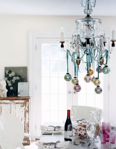 In the name of Holiday cheer love the glass ornaments hanging from chandelier with ribbon via Domino magazine