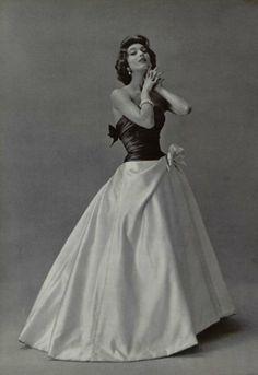 1956 Pierre Balmain. . Une large jupe dra- pée, en satin blanc, remonte sur le côté et s'orne d'un nœud en même satin. Le buste est moulé dans un corsage de satin gris foncé, qui, entièrement drapé, se termine lui aussi par un nœud dans le dos.