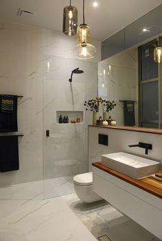 O banheiro cria um ambiente harmonioso e luxuoso com o box de vidro fixo