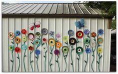 Jazz up your shed or fence with these fabulous Plate & Hose Garden Flowers. They're so easy to recreate yourself and a very clever way to disguise a plain fence or wall.