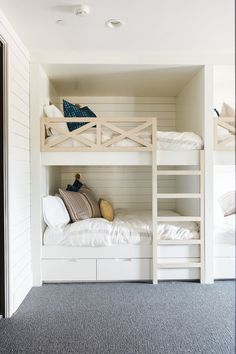 Built-in bunks with shiplap across the back, natural wood on the ladder, and railing details
