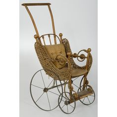 Victorian Wood and Wicker Doll Buggy  American, late 19/early 20th century, a wood and wicker doll buggy with metal wheels; ht. 24 in.