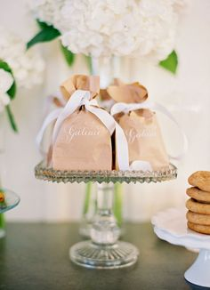 image: Jose Villa ~When I first looked at this I though it was a cake stand with a vase in the middle with guests bags sitting around it. I think the vase is behind the cake stand, but what I thought I saw could work nicely too. ~BC