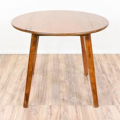 This rustic drop leaf table is featured in a solid wood with a glossy maple finish. This dining table is in good condition with 2 side drop leaves, a round curved table top and slanted tapered legs. Perfect for casual dining in a small space! #farmhouse #tables #diningtable #sandiegovintage #vintagefurniture
