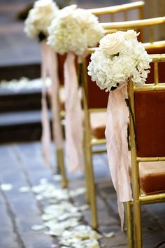 Small bunches of white hydrangeas and roses were tied to the chairs along the ceremony aisle.