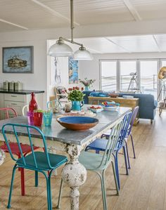 Open-plan Dining Room with Colourful Chairs Liven up an open-plan eating and dining space with pops of colour around a family table. Look for metal chairs in bucket-and-spade primary brights and a distressed zinc-topped table and make them the focal point of a light, white space. Bring in fresh flowers in colourful jugs and large vibrant platters. Experiment with lighting to add drama to the look - here an Art Deco-inspired ceiling light and large brass floor lamp give the room an industrial…