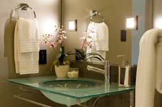 Ambiance Interiors: Chic, modern powder room design with mocha walls paint color, glass bathroom washstand, ...