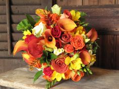 Bride:manngo calla lilies,rust roses,yellow fressia small white button mums,orange tea roses,montebretia orange,geranium leaves/galax leaves.  ADD:willow branch, a few orange tiger lilies to tie in the girls,and a few yellow roses the brides Fav! beutiful mix of fall flowers