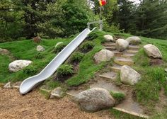 Natural Playgrounds Company built a slide into a constructed hill at an elementary school as shown here in Glens Falls, N.Y. The embankment slide is safer than tower slides with ladders. Scattered boulders, random dirt steps, rough terrain and varied plantings add to the rich textures and varied experiences on Natural Playgrounds.