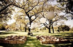 Rustic Outdoor Ceremony Wedding Decor with Hay Bale Seating and Large Hanging Paper Lanterns