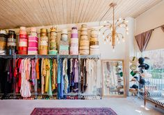 Textiles line the walls in showroom with chandelier