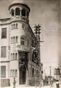 פועל חברת חשמל מתקין מנורת רחוב אל מול מלון גינוסר. השנה 1923