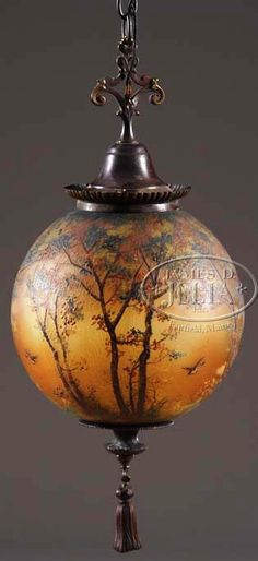 Handel Globe Hanging Lamp, birds in flight against iridescent orange background with trees in full foliage painted in hues of green, mauve and yellow. Globe is suppoted by a hardware which includes ceiling cap, top cap, harp and tassel. Connecticut, circa 1910-1930