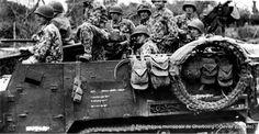 Soldats américains en tenue de camouflage dans un Half-track M2. Cette photo est donnée comme ayant été prise à Le Pont Brocard, hameau de Dangy (Manche),  le 28 juillet 1944, 41st Armored Inf. Regiment, 2nd Armored Division Le 27 juillet, la B Co, 41st AIR, 2nd US AD installe un road block pour bloquer le passage de la Soulles. Voir ici d'autres vues au même endroit : www.flickr.com/photos/mlq/817019996/in/pool-autresphotosn... et ici: www.flickr.com/se
