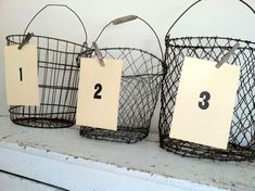 Old Wire Baskets...with handles...numbered cards attached with...old clothespins.