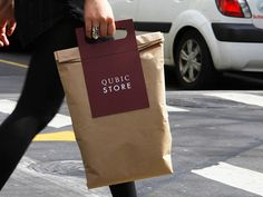 Qubic Store bags by Casey Ng. 'The Handle' has been specifically designed to accommodate garments of more or less any size. The purchase is folded inside selected wrapping paper and 'The Handle' is attached using self adhesive panels. In conjunction with a second component 'The Handle' can be adapted to carry shoe boxes of various sizes. #shopping #bag #packaging