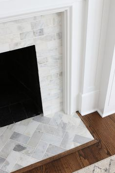 White Marble Tile Fireplace : Looking to update your old fireplace? This step-by-step process takes you through how we transformed our old fireplace into a white marble tile fireplace that we absolutely love. With a white mantle and marble tile. Fireplace Hearth Tiles, Fireplace Update, Old Fireplace, Marble Fireplaces, Fireplace Remodel, Fireplace Surrounds, Fireplace Design, Fireplace Ideas, Subway Tile Fireplace