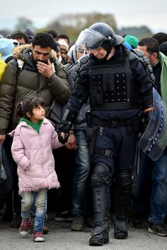 Refugees and migrants are escorted by police through Dobova as they are walked holding camp on October 22, 2015 in Dobova, Slovenia.
