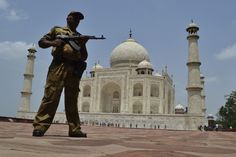A soldier from the Indian Central Industrial Security Force stands guard with his weapon drawn outside the Taj Mahal in Agra, India, on July 15, 2012.