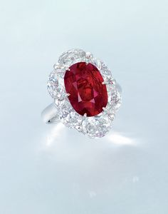 "Burma ""pigeon's blood red"" ruby and diamond ring. Set with an oval-shaped ruby weighing approximately 5.02 carats, within a similarly-cut diamond surround, mounted in 18k white gold."