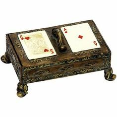 "Footed trinket box with king and ace accents.    Product: Card boxConstruction Material: Composite woodColor: Antique goldFeatures: King and Ace accentsDimensions: 4"" H x 7.75"" W x 5.25"" D"