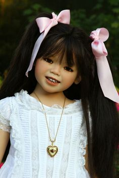 A doll by Annette Himstedt named Mei Mei, an Asian girl with long black hair, pink hair bows, a white dress, and a heart locket #Himstedt #doll