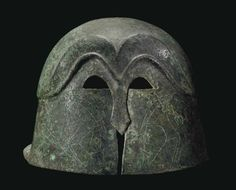 Corinthian helmet, pseudo Corinthian helmet, 5th century B.C.Formed of hammered sheet, of domed form, with a broad rear flange, the high-arching, M-shaped, raised eyebrows mirrored above and extending to the carinated ridge encircling the crown, the small false eye holes and nose-guard cut out and outlined with incised chevrons, the false cheek-pieces incised with confronting boars, 24.8 cm long. Private collection
