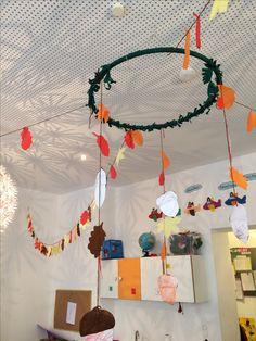 Guirnaldas de otoño hecha por los niños con hojas con papel seda y castañas pintadas