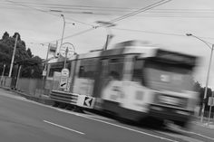 L1M2AS3. Tv Mode. BLURRED MOTION. 0.4sec, f/7.1, 70mm, ISO 100. Taken outdoors, tripod, ND filter as it was midday. Focus is on tram. Leading lines above and below the tram - tram cable and road lines- following tram's movement direction.