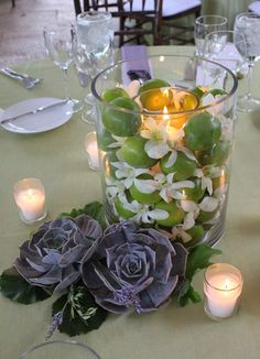 Large glass hurricane vases featured petite, white dendrobium orchids, tucked between rows of hand-selected fresh limes and lit from within by a single pillar candle.