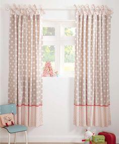 de beaux rideaux e beige et rose pâle à pois blancs dans la chambre de bébé