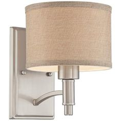 An oatmeal linen shade perfectly tones down the contemporary brushed nickel finish of this transitional wall sconce.