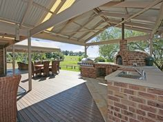 Beautiful outdoor entertainment area with kitchen including pizza oven and sink, overlooking the country side.