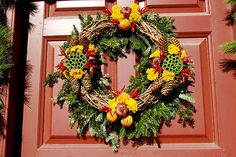 Red chili peppers help ward off the squirrels and birds that often feast on the decorations—another reason the wreaths aren't coated with any kind of acrylic or preservative in Colonial Williamsburg. Dried lotus seedpods, which typically are brown, are coated with green moss for a colorful twist.