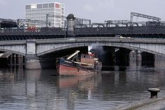 The Clyde puffer 'Stormlight' with her mast lowered passing under Glasgow's King George V Bridge.
