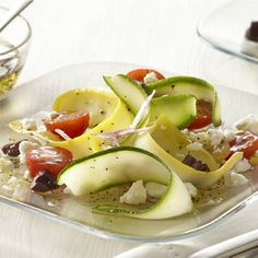 Ribbons of summer squash are dressed in a Greek vinaigrette for an appealing summertime salad. For effortless, paper-thin squash ribbons, use a vegetable peeler or a mandoline.