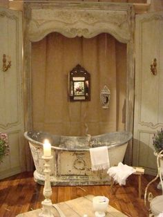 What is up with that dime store mirror?  I love the rustic yet elegance of the tub, cornice and walls.  A large, about 3 times larger, Venetian mirror would be gorgeous and also omit that hanging lantern.  I would like nice on the floor next to the tub with two other sizes for that romantic feel.